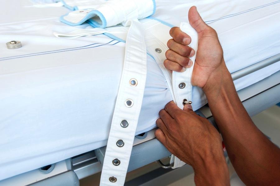 Des contentions sont installées par un professionnel de santé sur le lit d'un patient. (SPL/BSIP)